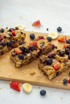 3 sliced oatmeal bars on a bamboo cutting board with extra fruit around the edge (vertical)