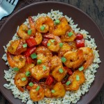 Pineapple shrimp stir-fry over a bed of rice garnished with green onion on a brown plate on a wooden surface with a towel and fork to the left side (with title overlay)