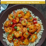 Pineapple Shrimp Stir Fry over a bed of rice on a round brown plate next to a brown towel with a fork all on a wooden surface (with title overlay)