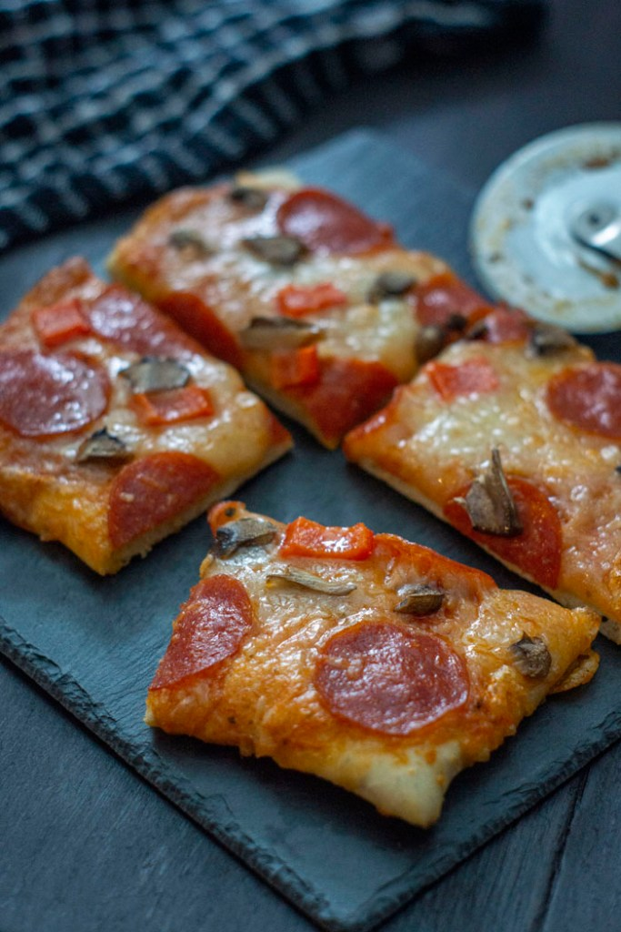 Pieces of pizza topped with sauce, cheese, pepperoni, and mushrooms on a slate serving plate next to a pizza cutter on a wooden surface (vertical)