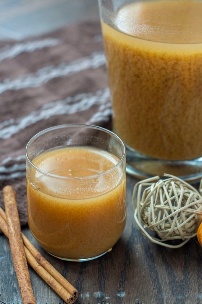 Pumpkin Juice in a small glass cup with a glass pitcher behind and cinnamon sticks to the side on a wooden surface (vertical)