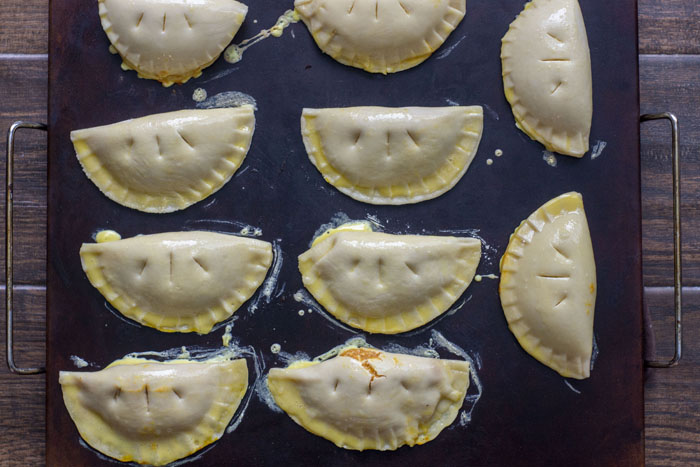 Prepared pumpkin pasties on a baking stone topped with an egg wash with three small slits in each all on a wooden surface