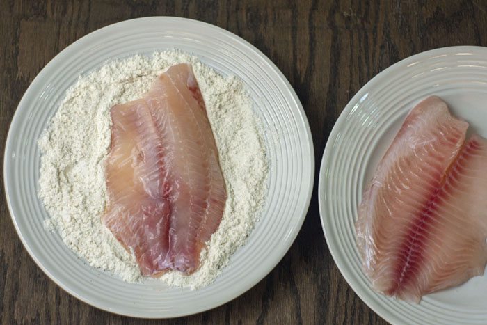 Two white plates on a wooden surface, one with a single filet of tilapia, the other with tilapia resting in flour