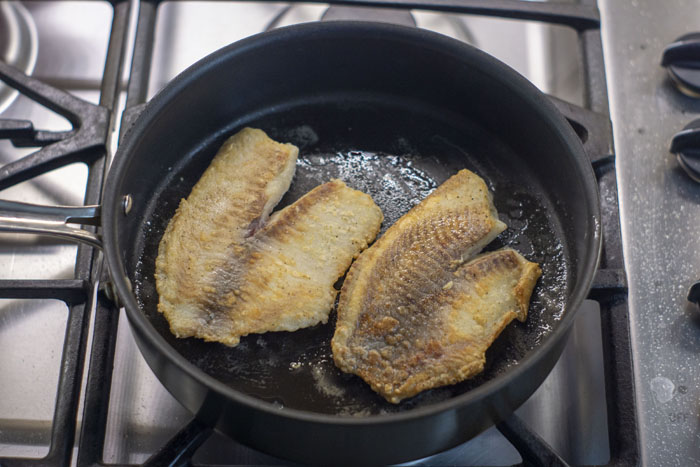 Skillet with two fillets of tilapia cooking over a gas stovetop