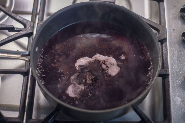 Skillet with pinot noir simmering over a gas stovetop