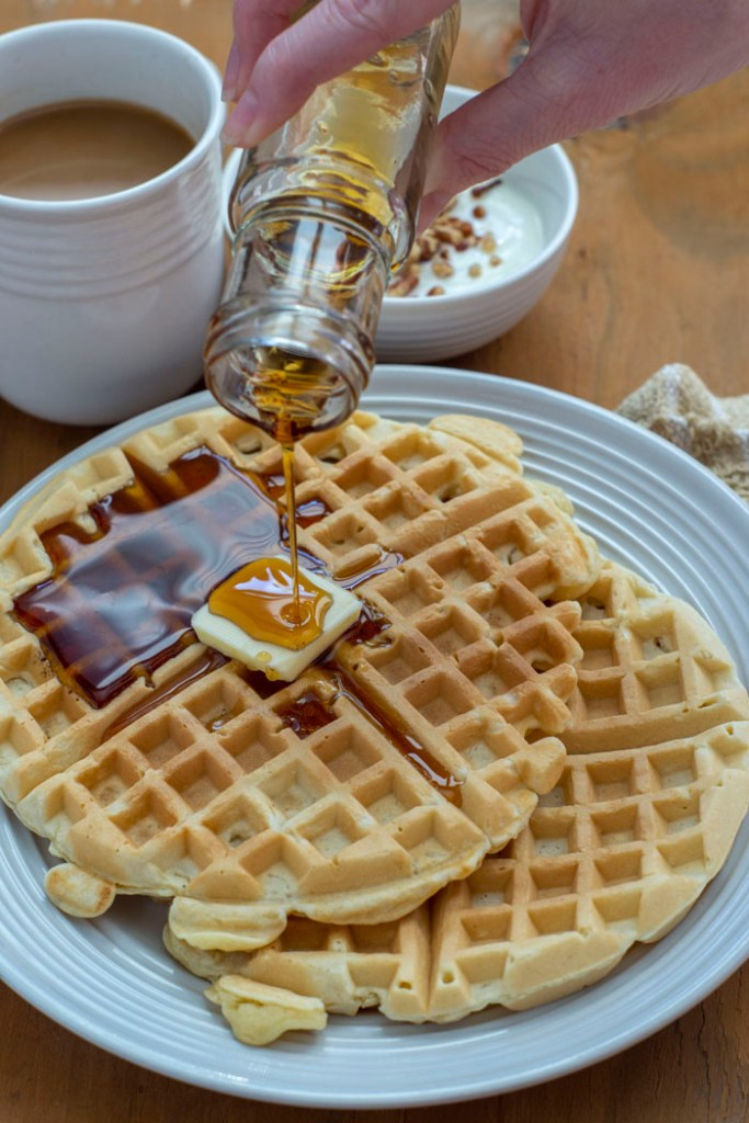 Two waffles with a pat of butter on a white plate with syrup pouring onto them and a cup of coffee and a yogurt parfait in the background on a wooden surface (vertical)