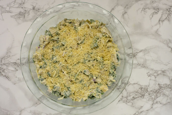 Spinach artichoke dip covered with shredded cheese in a glass pie pan on a white and grey marble surface