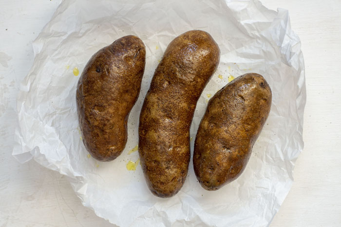 3 brown potatoes covered with oil, salt, and pepper sitting on a piece of parchment paper on a white surface