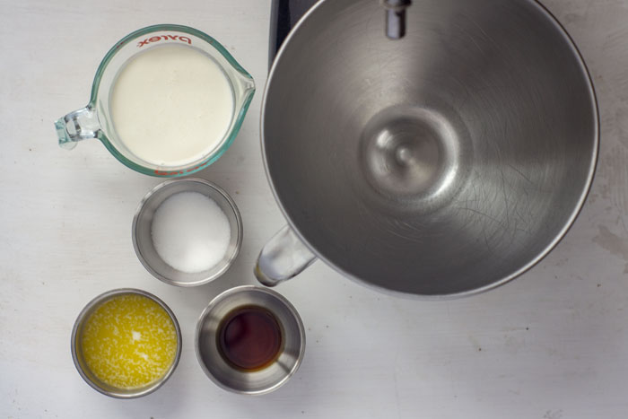 Stainless steel mixing bowl for stand mixer next to three small stainless steel bowls with melted butter, sugar, and vanilla extract next to a glass measuring cup with heavy cream all on a white surface