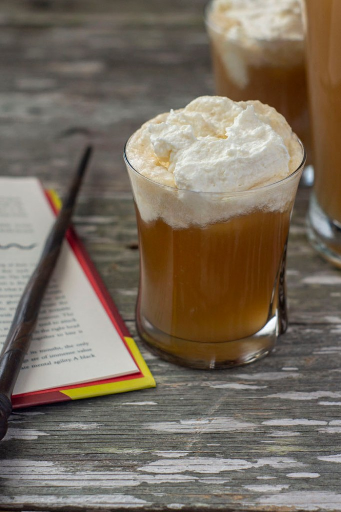 Glass of Butterbeer topped with whipped topping next to an open book and a magic wand with a pitcher of Butterbeer in the background all on a wooden surface (vertical)