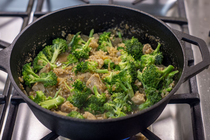 Large cast-iron pan with chicken, onion, rice, broth, and broccoli over a gas stovetop