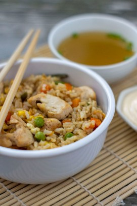 Chicken fried rice in a white bowl with wooden chopsticks across the top next to a bowl of clear onion soup and a small dish of white sauce on a bamboo placemat (vertical)