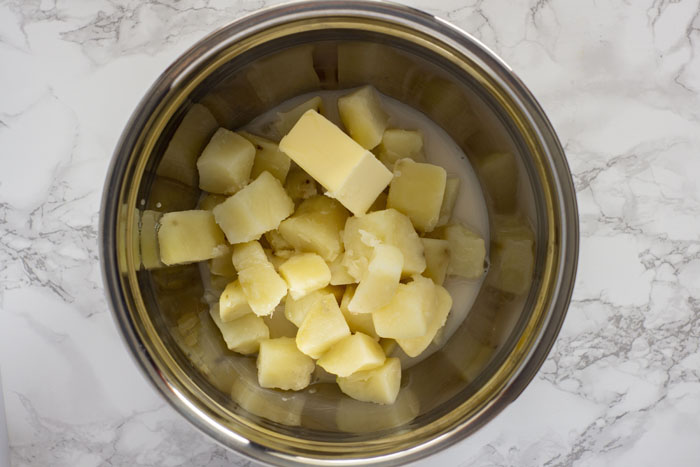 Cooked potatoes peeled and chopped in a large stainless steel mixing bowl with milk and butter all on a white and grey marble surface