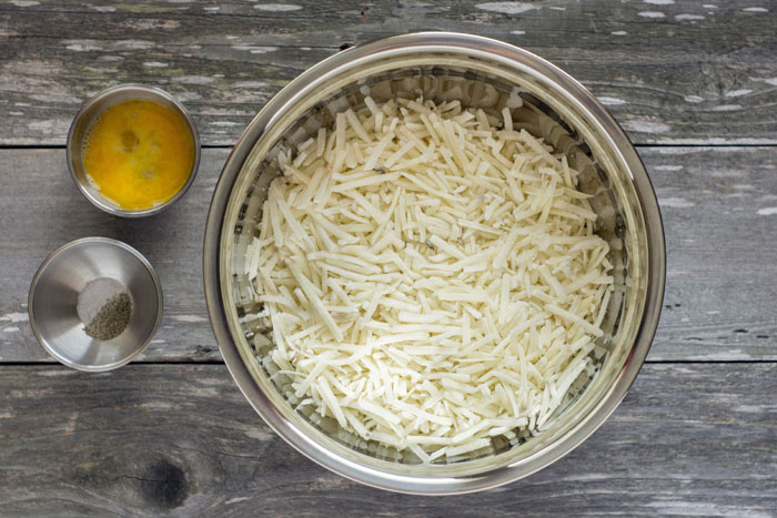 Large stainless steel bowl with hash browns next to small stainless steel bowls of eggs and seasonings on a wooden surface