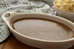 Homemade brown gravy in an oval white dish next to a white bowl of mashed potatoes with a white and green towel behind all on a wooden surface