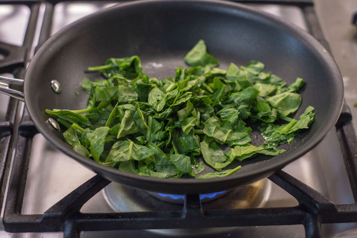 Spinach leaves wilting in a small saute pan over a gas stovetop