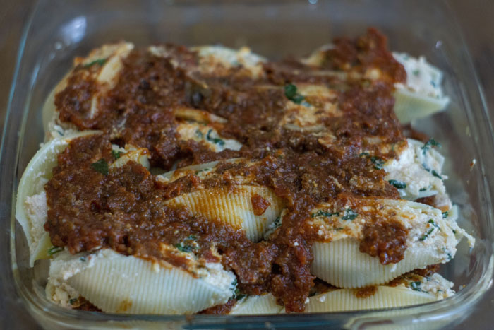 Glass baking dish with two layers of stuffed shells covered with marinara sauce