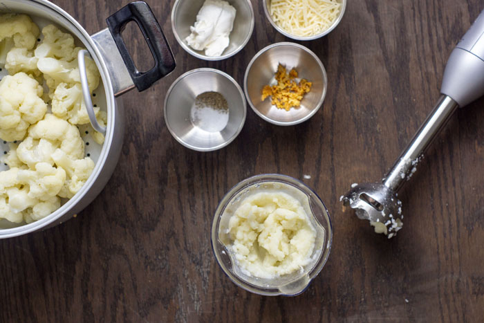 Cauliflower in a metal steamer pot next to stainless steel bowls with cream cheese, parmesan cheese, seasonings, and roasted garlic near a container with mashed cauliflower next to an immersion blender all on a wooden surface