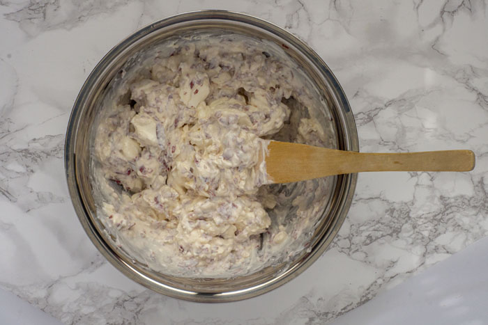 Hot Virginia Dip mixed in a stainless steel mixing bowl with a wooden spoon on a white and grey marble surface