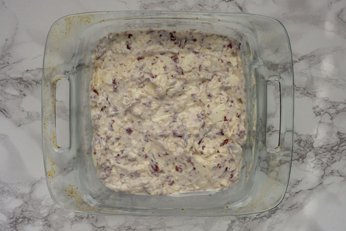 Hot Virginia Dip spread out in a glass baking dish on a white and grey marbled surface