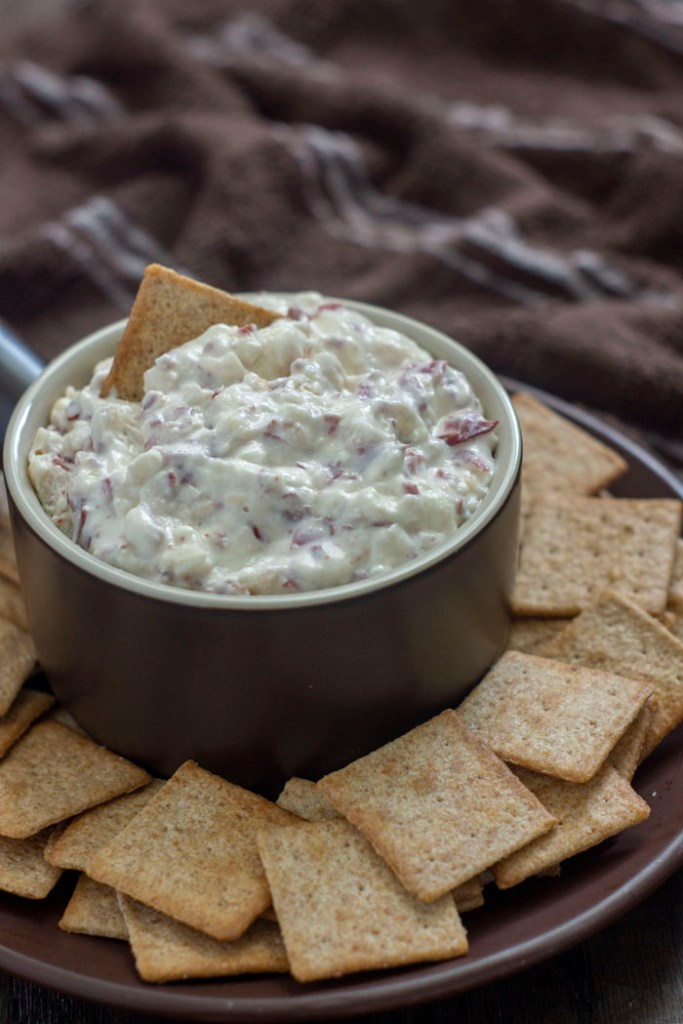Hot Virginia Dip in a brown dish with crackers around the bowl and a brown towel in the background (vertical)