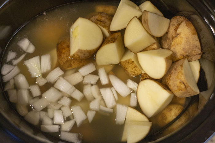 Slow cooker with broth, potatoes, and diced onions