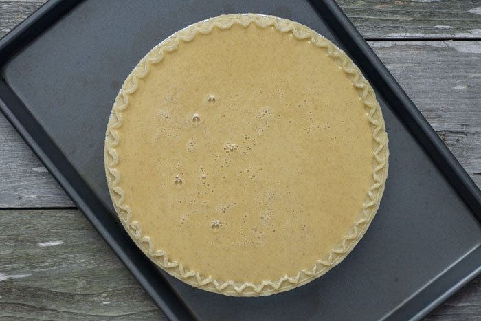 Pumpkin pie filling mixed together in a pie crust on a metal sheet pan on a wooden surface