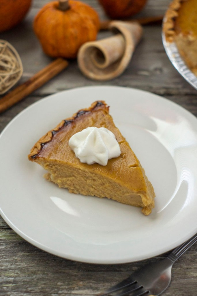 Slice of pumpkin pie topped with whipped cream on a round wooden plate in front of fall decorations on a wooden surface (vertical)