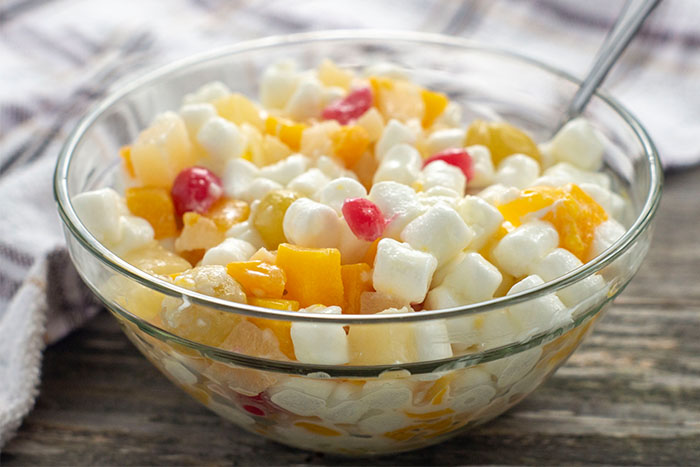 Ambrosia salad in a clear glass bowl in front of a white and brown towel all on a wooden surface