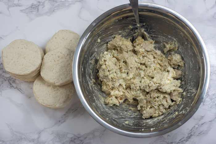 Stainless steel bowl of chicken biscuit filling mixture with a spoon in the bowl next to a pile of uncooked biscuits on a white and grey marble surface