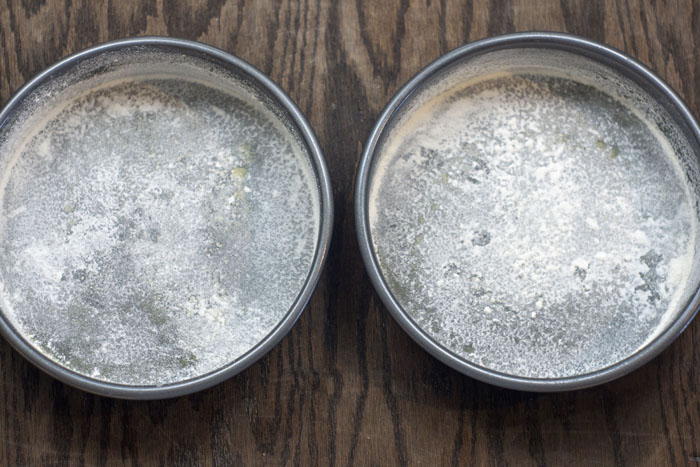 Two round metal cake pans covered in oil and flour on a wooden surface
