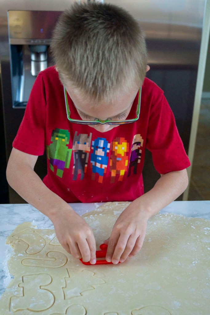 Young boy using a red cookie cutter to make shapes in rolled cookie dough on a white and grey marble surface