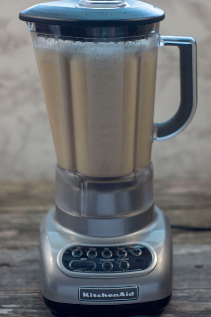 Coquito being blended in a blender sitting on a wooden surface