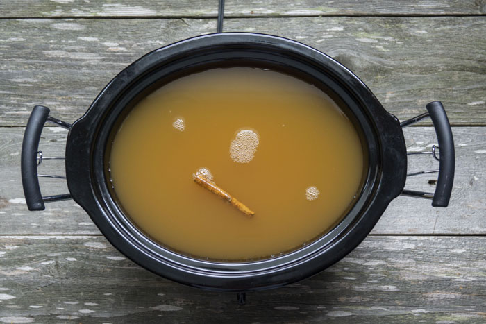 Apple cider with cinnamon sticks in a slow cooker on a wooden surface