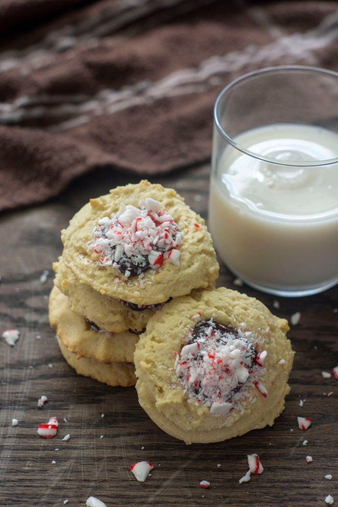 Stack of peppermint chocolate ganache thumbprint cookies surrounded by crushed peppermint and a glass of milk and brown towel behind all on a wooden surface (vertical)