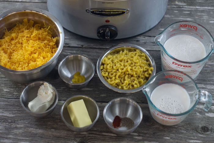 Slow Cooker Mac and Cheese ingredients: Stainless steel bowls with shredded cheddar cheese, mustard, cream cheese, butter, macaroni noodles, and seasonings next to measuring cups of milk and half-and-half with a slow cooker behind all on a wooden surface