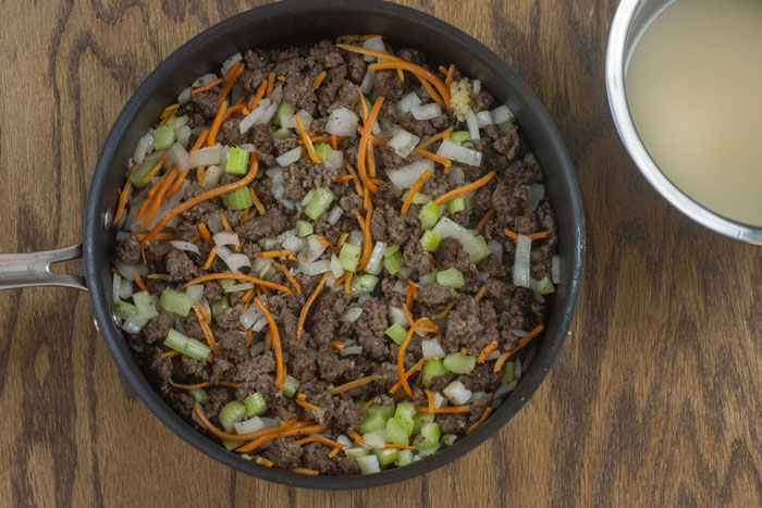 Large skillet with browned ground beef and vegetables next to a stainless steel bowl with broth on a wooden surface