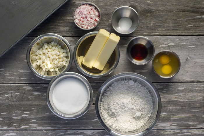 Ingredients for White Chocolate Blondies with Peppermint Frosting: Stainless steel bowls each with white chocolate chips, crushed peppermint, salt, vanilla extract, eggs, flour, sugar, and butter next to a metal baking dish all on a wooden surface