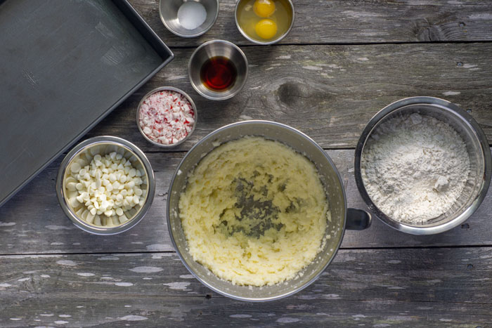 Large mixing bowl with combined sugar and butter next to stainless steel bowls with flour, white chocolate chips, crushed peppermint, vanilla extract, eggs, and salt next to a metal baking dish all on a wooden surface