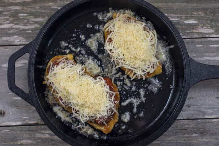 Cast iron skillet with fried chicken breasts covered with red sauce and shredded cheeses all on a wooden surface