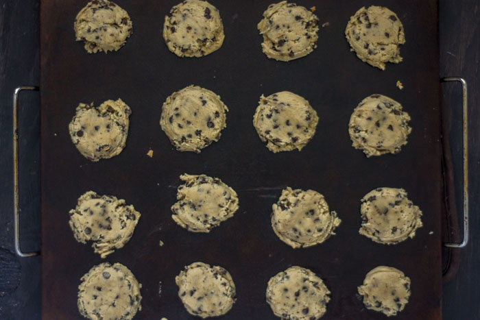 Baking stone with flattened scoops of cookie dough on a wooden surface