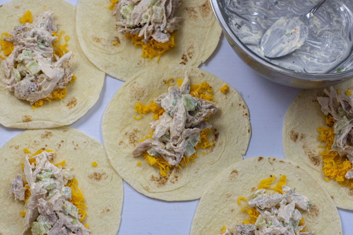 Tortilla shells laid out next to each other with shredded cheddar cheese and chicken mixture in the center of each next to an empty stainless steel bowl all on a white surface