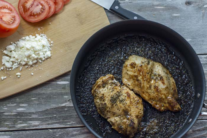 Bamboo cutting board with sliced tomato and crumbled feta next to a skillet with cooked chicken in balsamic vinaigrette on a wooden surface