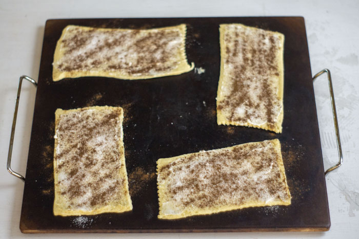 Baking stone with rectangular crescent rolls covered in butter and sprinkled with sugar and cinnamon on top on a white and grey surface
