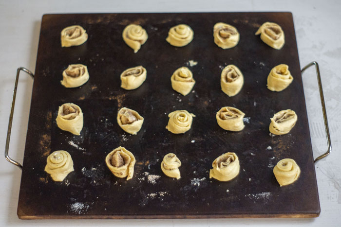 Baking stone with sliced cinnamon crescent rolls on top of a white and grey surface
