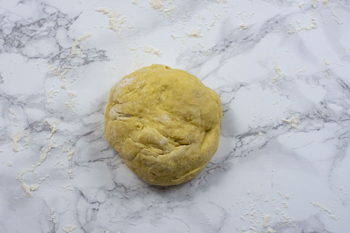 Ball of paczki dough on a white and grey marble surface