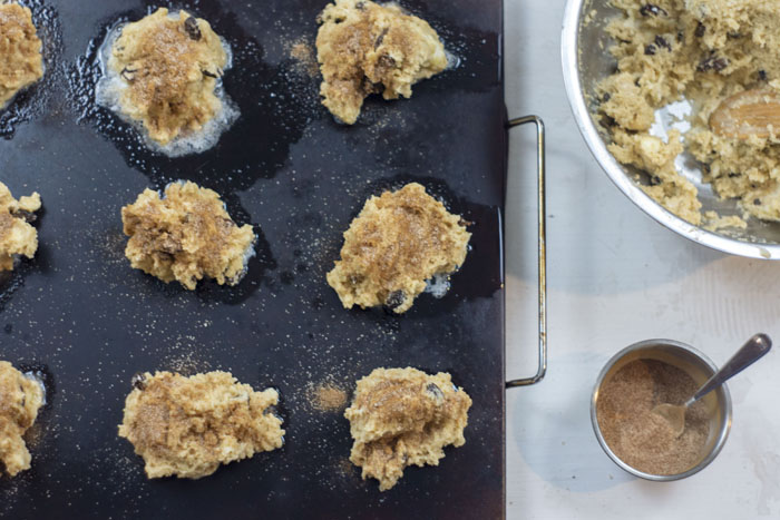 Rock cake dough on a baking stone next to a stainless steel bowl of dough and a small stainless steel bowl with cinnamon sugar all on a white surface