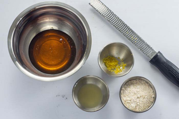 Stainless steel mixing bowl with golden syrup next to stainless steel bowls of lemon juice, lemon zest, and oat flour with a lemon zester all on a white surface