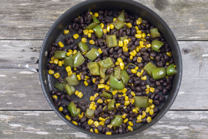 Diced green peppers, corn kernels, and black beans in a large nonstick skillet over a wooden surface