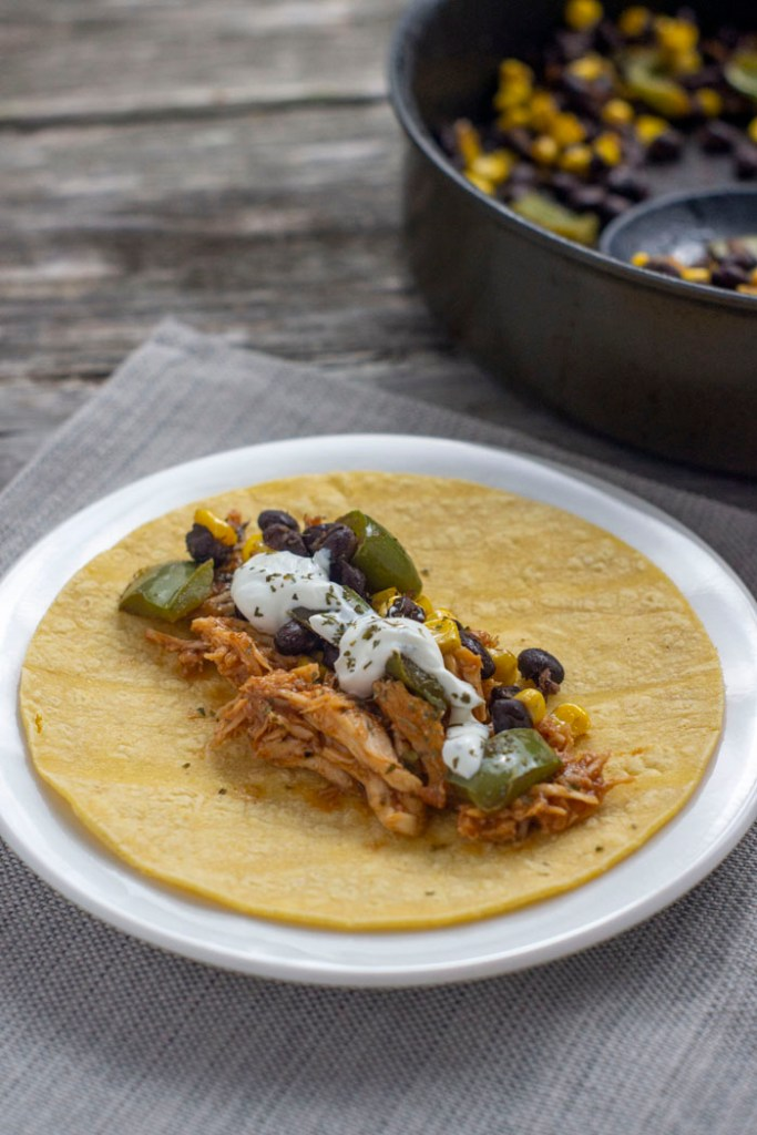 BBQ chicken and black bean taco fillings on a corn tortilla on a round white plate on a grey placemat next to a nonstick skillet with taco fillings all on a wooden surface (vertical)